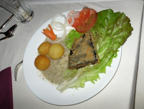 ein Bild mit nem Teller mit Kartoffelbällchen, Tomatenscheiben und Fisch der auf nem riesigen Salatblatt liegt