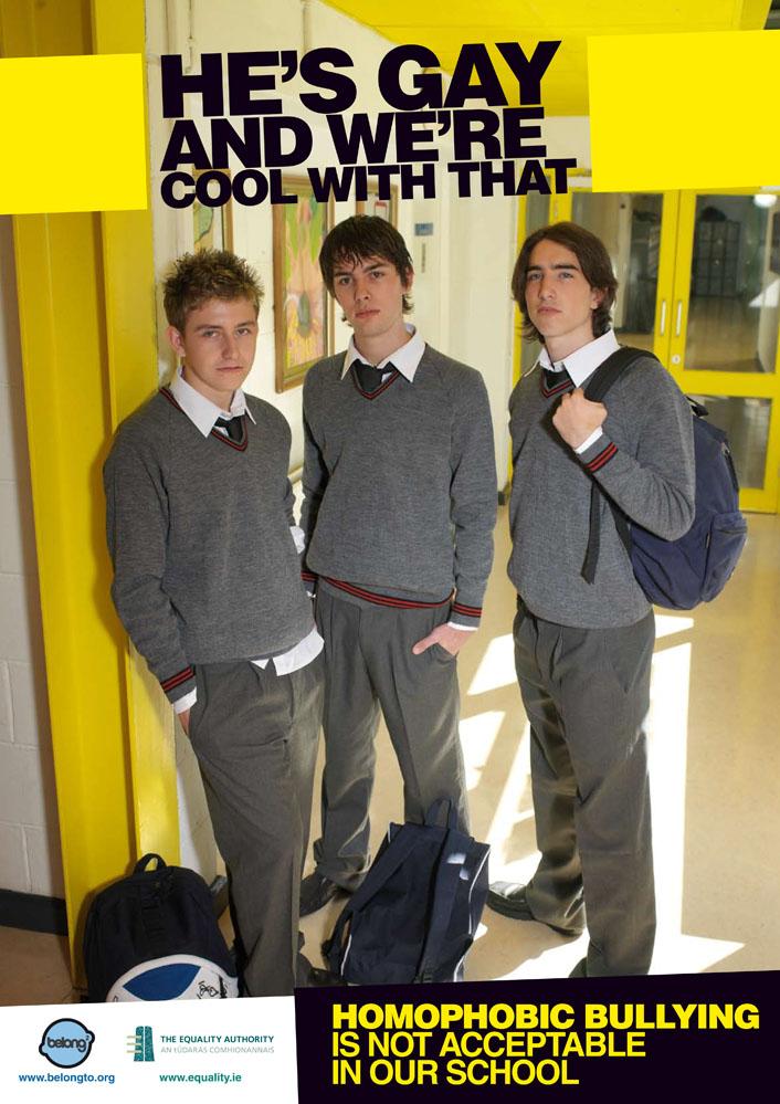 Ein Plakat einer irischen Kampagne belongto.org mit drei Personen in Schuluniform. Auf Englisch: Er ist schwul und das ist für uns okay. Alle drei stehen nebeneinander und schauen sich wechselseitig an. So weiß mensch gar nicht, wer denn überhaupt gemeint ist. Unten steht homophobes mobbing wird an unserer Schule nicht akzeptiert.